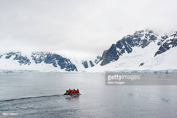 Group of people crossing the ocean in the Antarctic in a rubber boat, snow-covered mountains in the background.