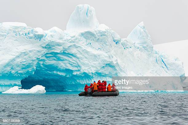 group of people crossing the ocean in the antarctic in a rubber boat, icebergs in the background. - 南極大陸探検 ストックフォトと画像