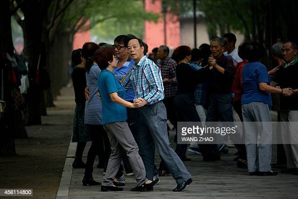 A group of people dance at a park in Beijing on September 26 2014 A report in local media said that China's young adults are gaining more weight and...
