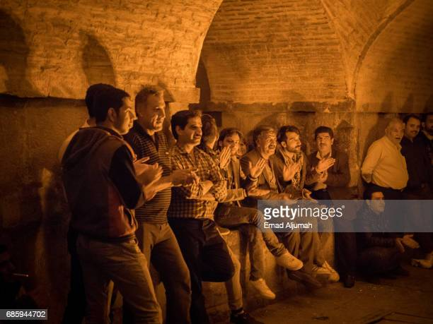 a group of people dancing and singing traditional songs under khaju bridge in esfahan at nightfall - 26 april 2017 - ハージュ橋 ストックフォトと画像
