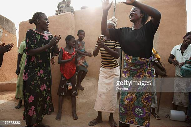 group of people dancing in their mud compound - african tribal culture stock pictures, royalty-free photos & images