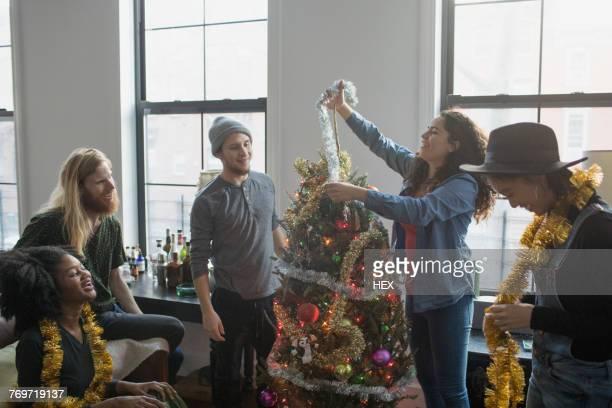 a group of people decorating a christmas tree - alleen volwassenen stockfoto's en -beelden