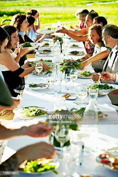 Group of people dinning at table outside in field