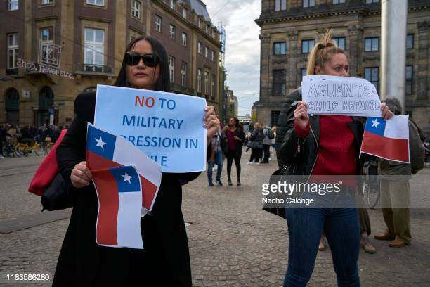 A group of people display placards in protest of the Chilean government's repression during the demonstration organized today in Amsterdam in support...