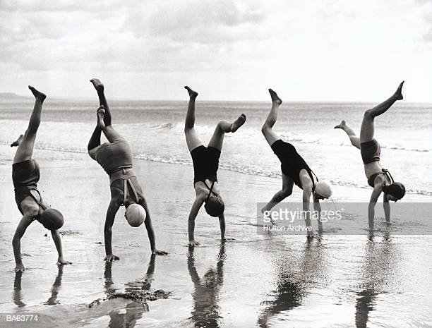 Group of people doing handstands on beach (B&W)