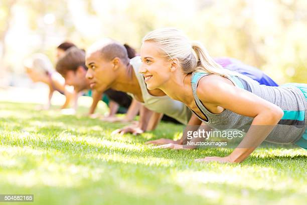 Group of People Doing Push-Ups At Bootcamp Workout Class