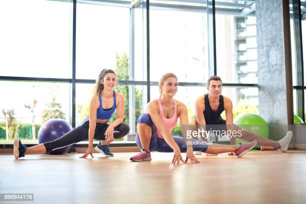 group of people doing streching in a class in a gym - legs spread woman stock photos and pictures