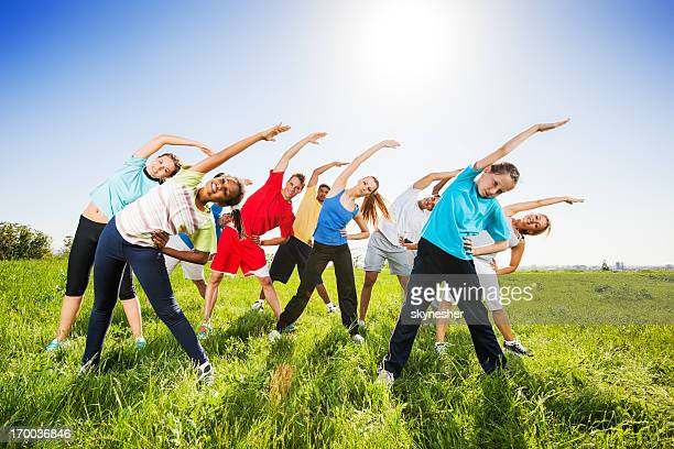 Group of people doing stretching exercises in field.