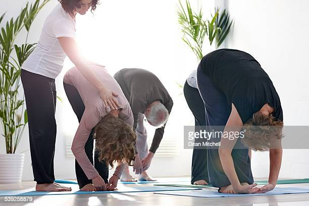 group of people doing stretching workout at fitness club - teacher bending over stock photos and pictures