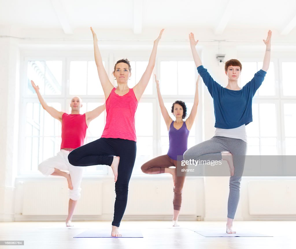 Group of people doing the yoga tree position : Stock Photo