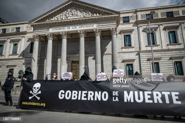 Group of people dressed as the grim reaper protest with a giant banner against the euthanasia law in front of the congress of deputies on March 18,...