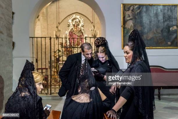 Group of people dressed in a very old fashion way with the traditional 'mantilla' and 'peineta' chatting inside a church In Seville during what is...