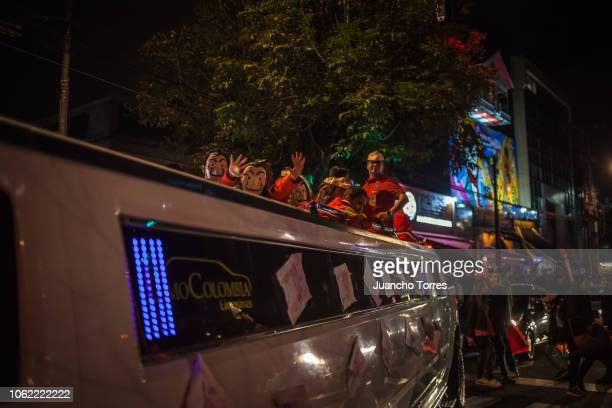 A group of people dressed in La Casa de Papel costumes wave from a limo during the zombie parade to demand for a better and quality education and to...