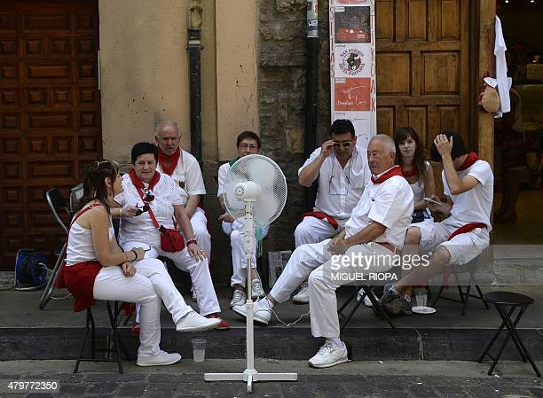 A group of people dressed in traditional red and white clothes sit around a fan to cool off themselves in Pamplona northern Spain on July 7 during...