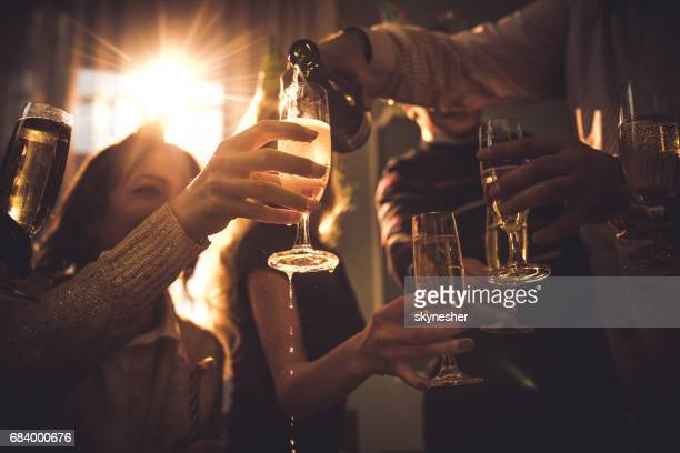 group of people drinking champagne on a party at home. - pouring stock photos and pictures