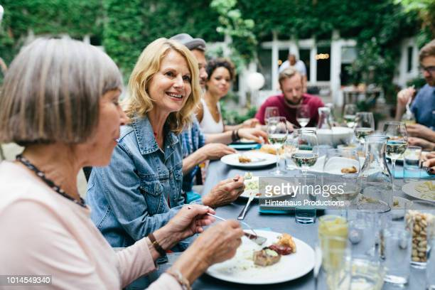 group of people enjoying an outdoor meal together - barbecue social gathering stock pictures, royalty-free photos & images