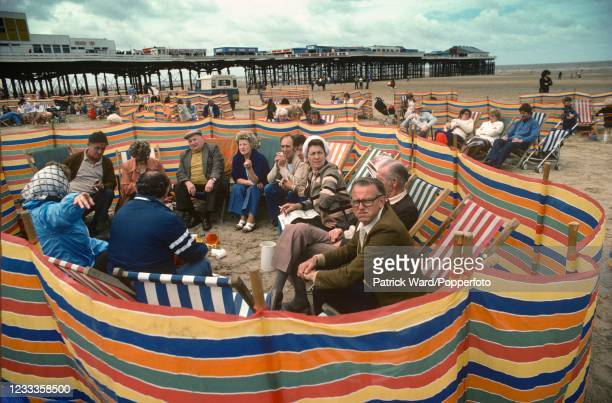 Group of people enjoying their holiday on Blackpool Beach, circa August 1985.