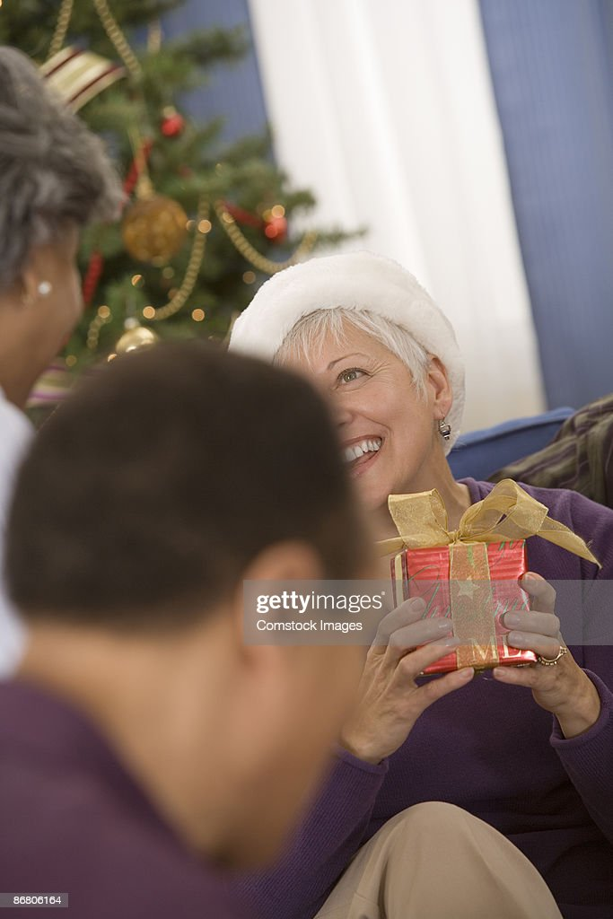 Group of people exchanging gifts at a christmas party : Stock Photo