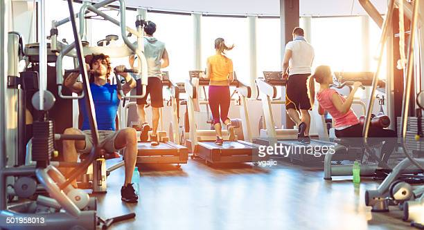 group of people exercise in a gym. - exercise equipment stock pictures, royalty-free photos & images