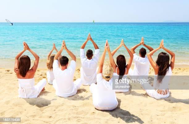 Groupe de personnes d'yoga sur la plage.
