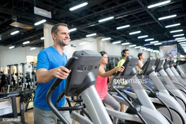Groep mensen trainen op de sportschool op cross-trainers