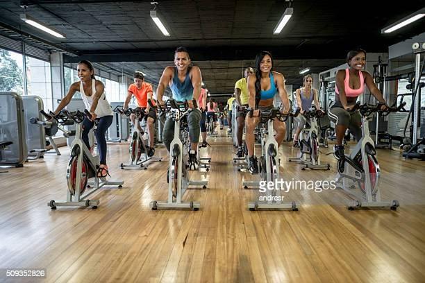 group of people exercising at- the gym - spinning stock pictures, royalty-free photos & images