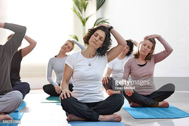 group of people exercising in yoga class - neck stock photos and pictures