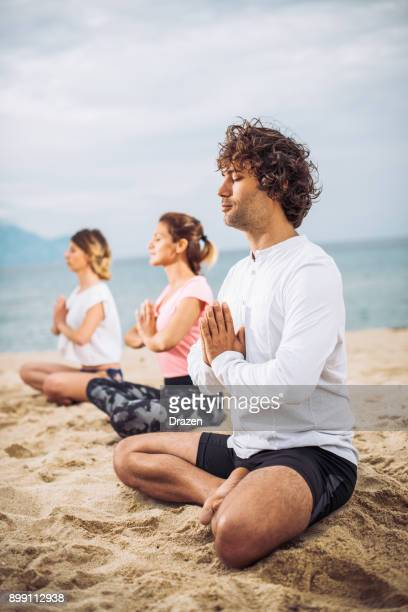 Group of people exercising on the beach and practicing yoga during the summer holiday