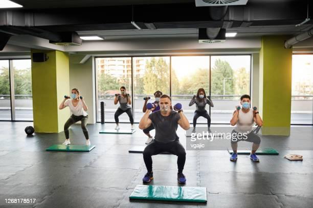 ジムで男性トレーナーと一緒に運動する人々のグループ - ビジネスを再開 - エクササイズクラス ストックフォトと画像