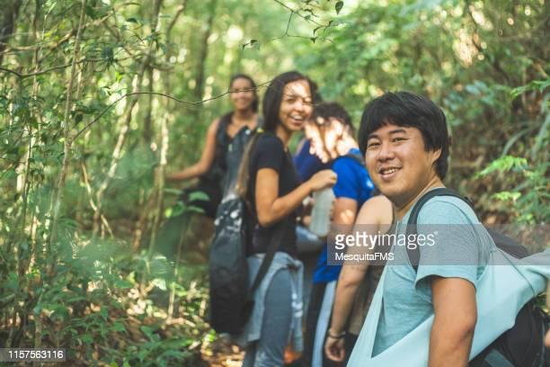 森を探検する人々のグループ - ツアーガイド ストックフォトと画像