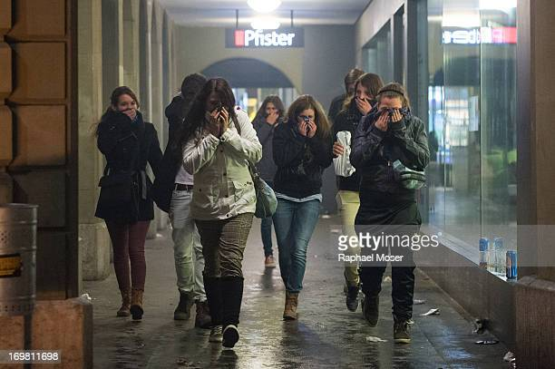 Group of people fleeing and trying to cover their faces from tear gas in the center of Switzerland's capital Bern during the 3rd edition of 'Tanz...