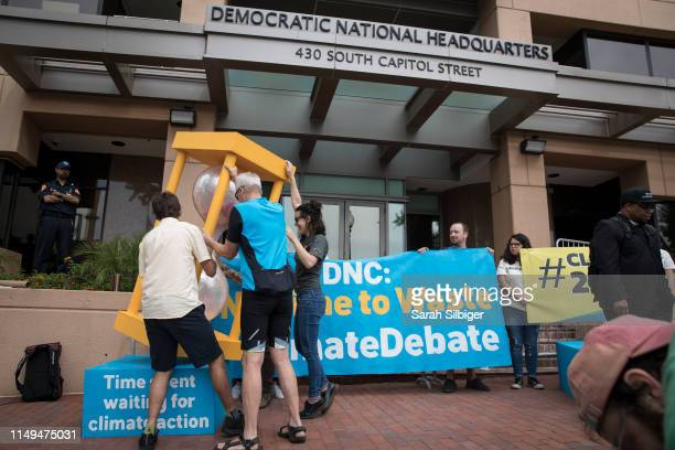 A group of people flip over an hourglass in front of the Democratic National Committee headquarters during a Green Peace rally to call for a...