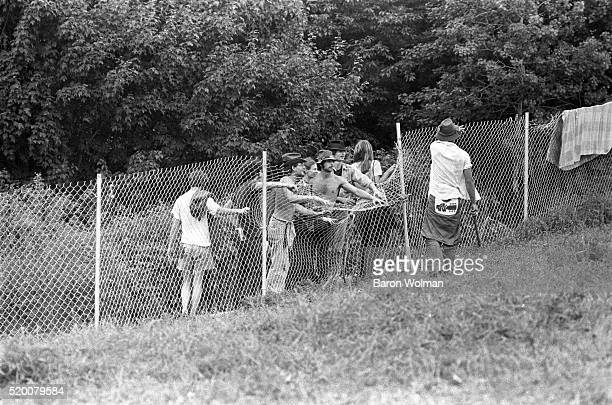 A group of people force a fence at the Woodstock Music Art Fair Bethel NY August 15 1969