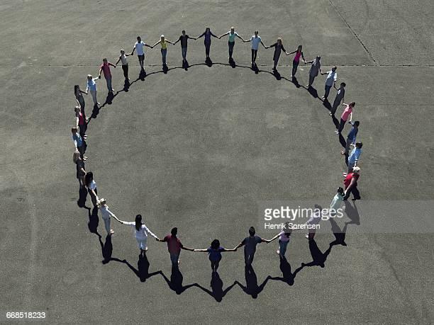 group of people forming a circle - darsi la mano foto e immagini stock