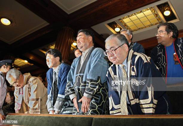 A group of people from Japan's minority Ainu people bow their heads after the Japanese parliament recognised the Ainu as an indigenous people at the...
