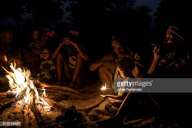 Group of people from the San tribe also known as 'bushmen' sitting around the fire at night to smoke and tell stories