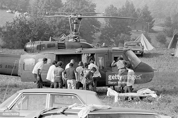 A group of people gather around a US Army helipoter at the Woodstock Music Art Fair Bethel NY August 15 1969
