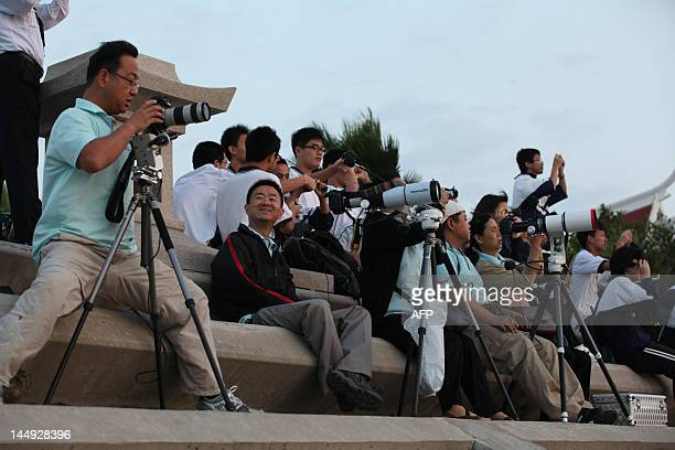 A group of people gather to watch the annular solar eclipse on the coast of Xiamen in China's southeast province of Fujian on May 21 2012 Millions...