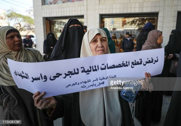 A group of people gather with a call of The Committee for Families of Martyrs in the Gaza Strip to protest against the cutting the stipends for...