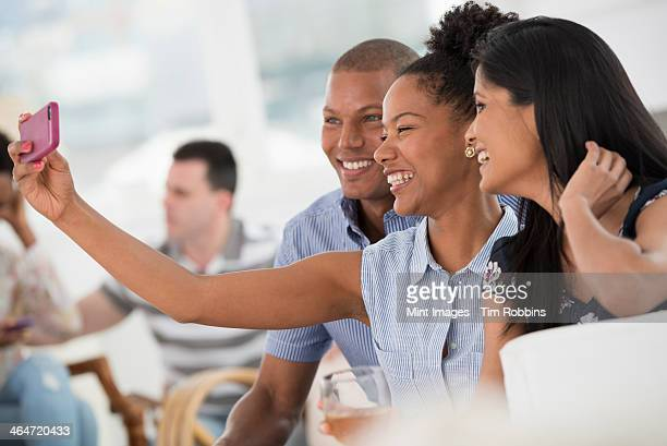A group of people gathering together for a party or an office event. A woman taking a selfie of the group with a smart phone.