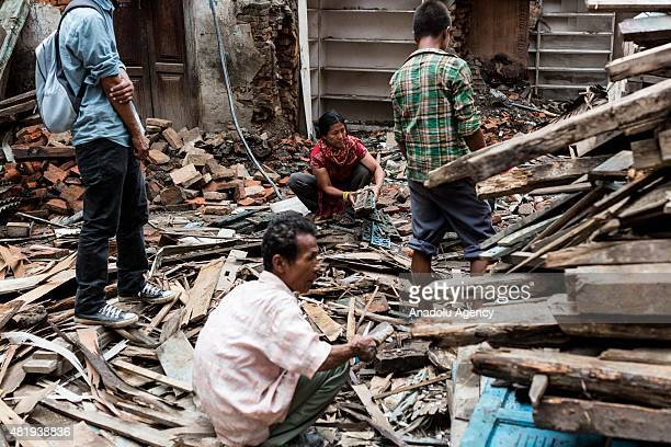 Group of people go through debris from a destroyed building in Kathmandu on July 25, 2015. Today marks the 3 month anniversary of the Nepal...