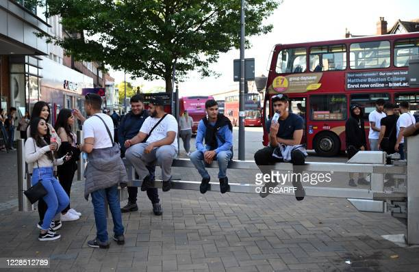 Group of people hang around a pedestrianised street in Solihull, central England on September 14, 2020 after the British government imposed fresh...