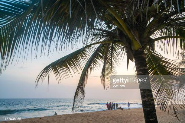 A group of people hangout on the beach looking out into the waves Monrovia Liberia