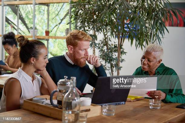 group of people having a meeting in an open plan office - sally anscombe stock pictures, royalty-free photos & images