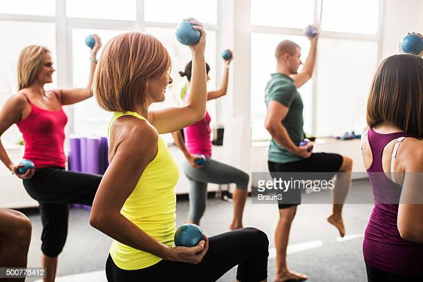 Group of people having a Pilates exercises with weight balls.