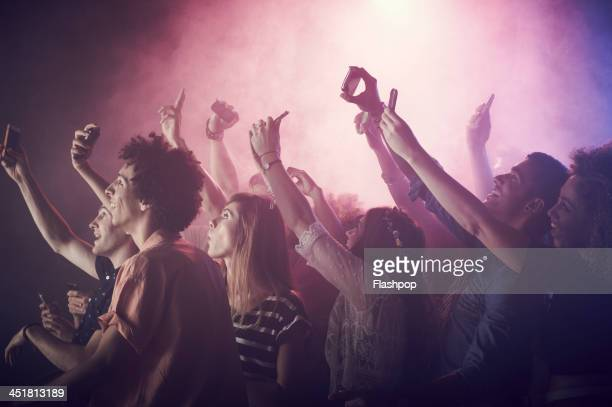 group of people having fun at music concert - concert photos et images de collection