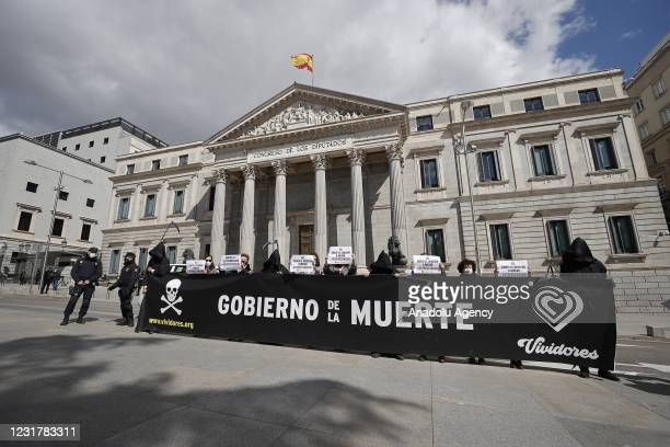 """Group of people hold a banner reading """"Government of Death"""" during a protest against euthanasia after the law drafted at the initiative of the left..."""