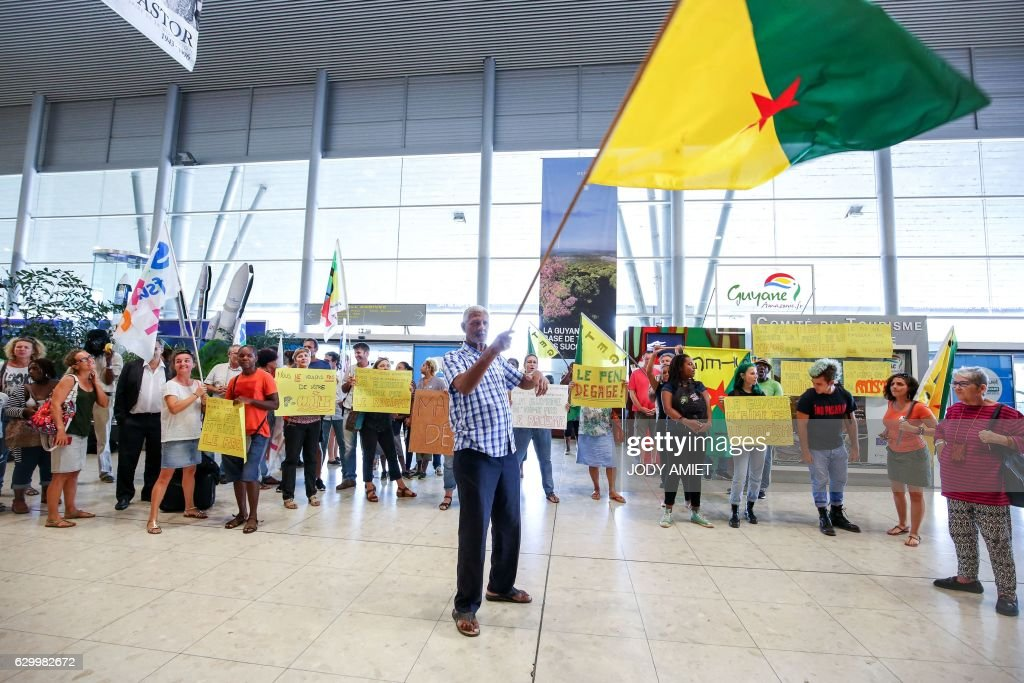 A group of people hold placards and the French Guiana national flag as they chant slogans during a gathering of anti-Marine Le Pen at the Felix Eboue airport as they wait for the arrival of the French far-right Front National (FN) party president and candidate for France's 2017 presidential election, in Cayenne, on December 15, 2016. / AFP / jody amiet