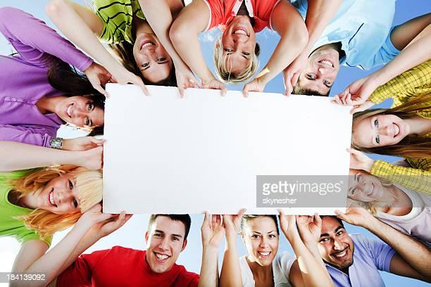 Groupe de personnes tenant un grand tableau blanc pour publicité.