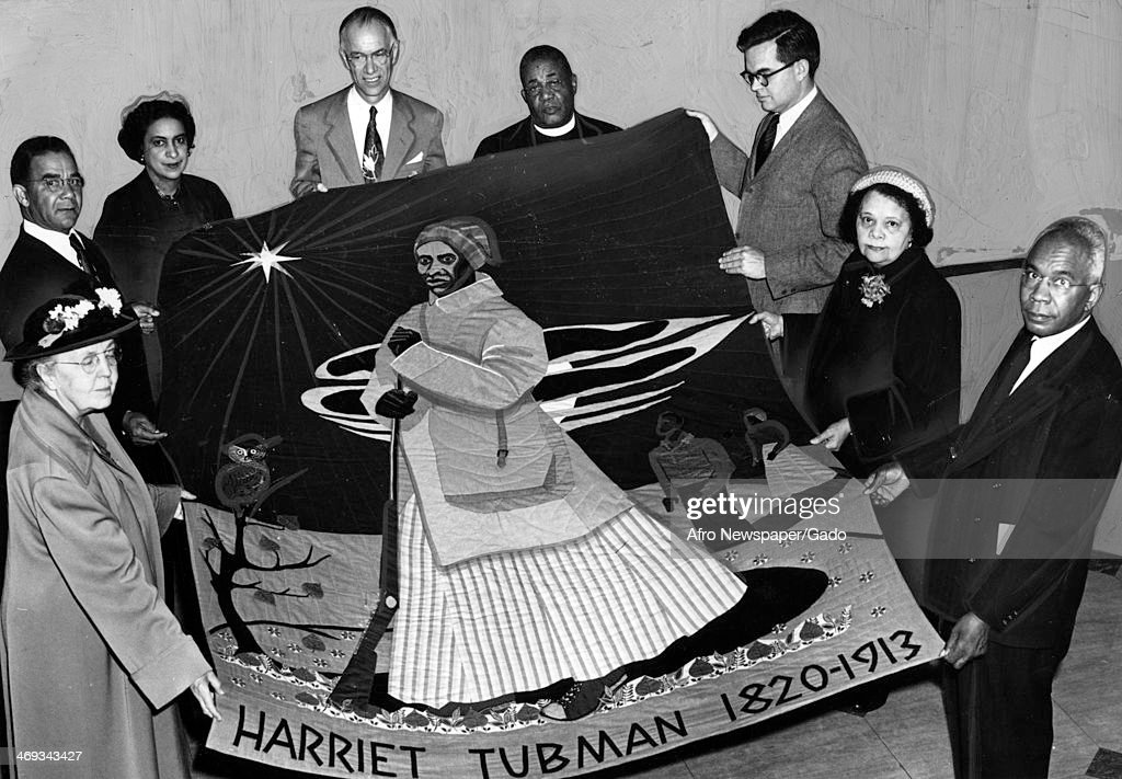 A group of people holding a tapestry with a portrait of Harriet Tubman, born Araminta Harriet Ross, 1820 1913, a former slave and abolitionist and humanitarian, 1950.